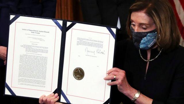 Nancy Pelosi mostrando la acusación contra Donald Trump
