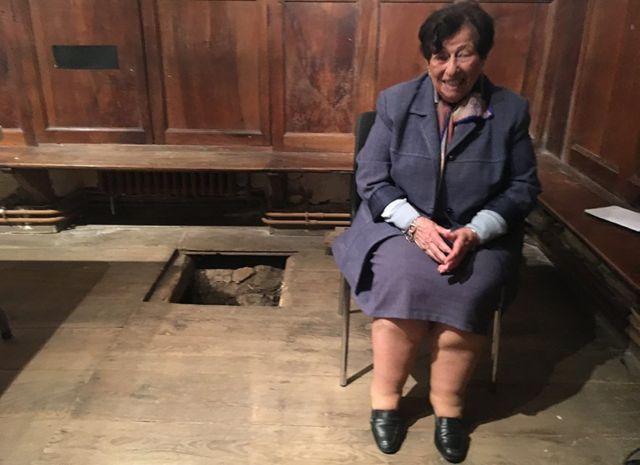 Annie junto a la trampilla de la capilla.