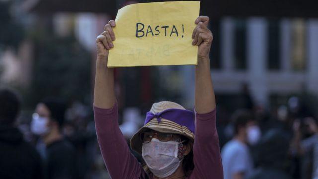 Mulher de chapéu e máscara segura cartaz dizendo 'basta' na Avenida Paulista