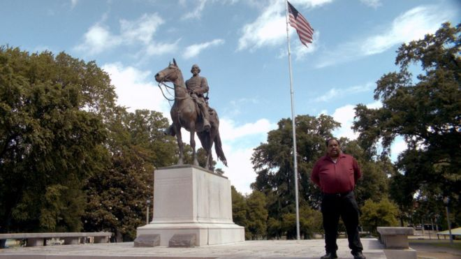 Daryl Davis em frente a um monumento e uma bandeira dos EUA
