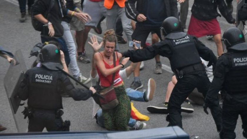 Policemen hit a protester with batons outside El Prat airport in Barcelona