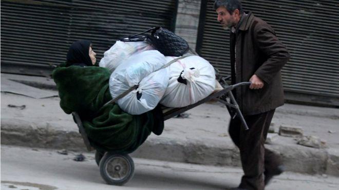 Ein Mann schiebt einen Wagen eine ältere Frau und Hab und Gut, wie sie fliehen tiefer in die verbleibenden Rebellen kontrollierten Gebiete in Aleppo, Syrien 12. Dezember 2016 trägt.