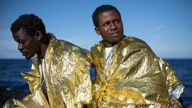 """West African men relax on the deck of the Topaz Responder, MOAS"""", Migrant Offshore Aid Station search and rescue vessel as it makes its way to Vibo Valentia, in Italy November 23, 2016 in Pozzollo Italy."""