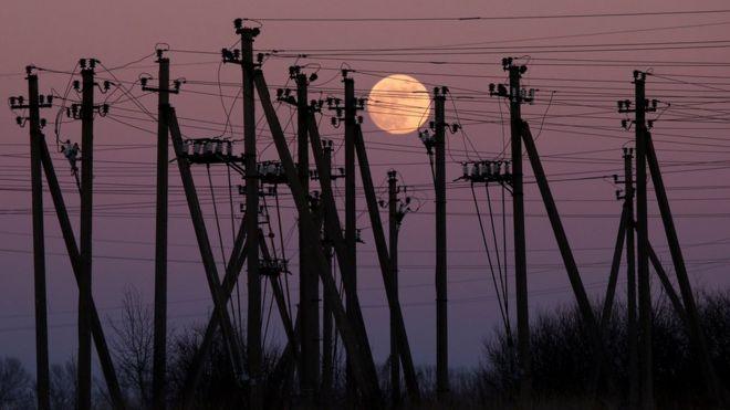A full moon is seen rising through electric poles near Virbalis, Lithuania February 10, 2017