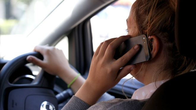 Woman using mobile phone while driving (posed by model)