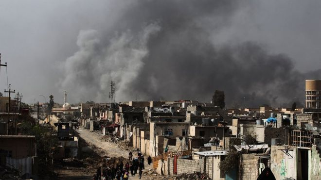 """Iraqi families leave Mosul """"s Nablus neighbourhood on March 12, 2017, during an offensive by security forces to retake the western parts of the city from Islamic State (IS) group fighters."""