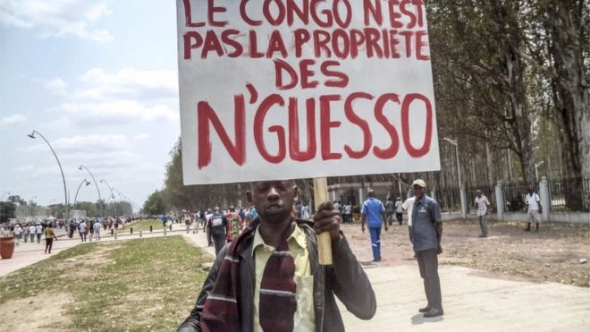 "A man holds a placard reading ""Congo is not the property of N""Guesso"" during an opposition demonstration in Brazzaville - 27 September 2015"