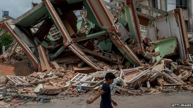 A man walks past rubble following the second quake on 13 May, 2015
