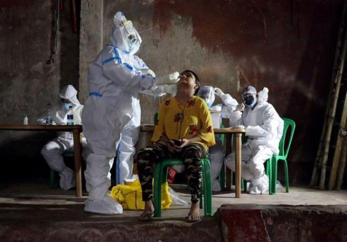 Un travailleur de la santé portant un équipement de protection individuelle prélève un échantillon sur une femme