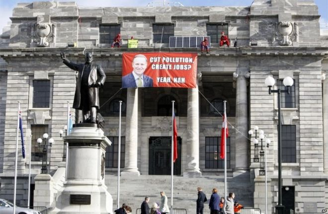 Four Greenpeace environmental protesters perch themselves on a ledge above the main entrance of parliament buildings in Wellington, New Zealand, Thursday, June 25, 2015.
