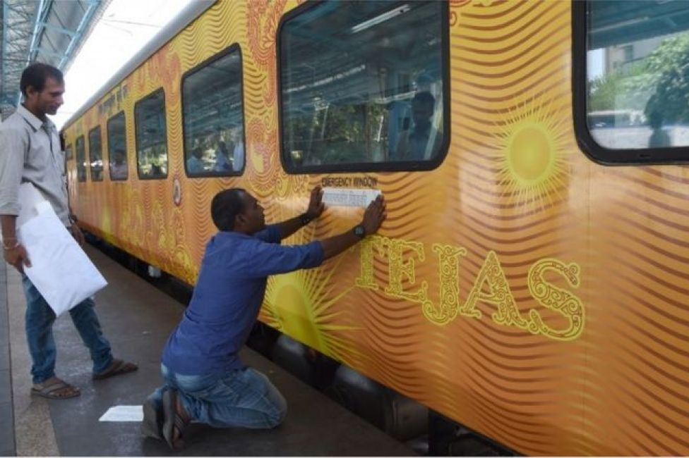 In this photograph taken on May 21, 2017, Indian staff paste stickers below an emergency window of the Tejas Express luxury train before its first journey between Mumbai and Goa at the Chattrapati Shivaji Terminus terminus station in Mumbai.