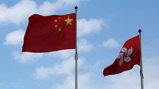A Chinese national flag and a Hong Kong flag fly outside the Legislative Council in Hong Kong