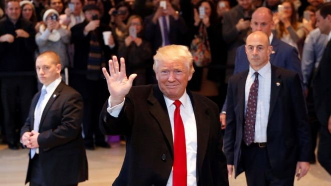 Donald Trump waves to the crowd as he leaves the New York Times building following a meeting, 22 November