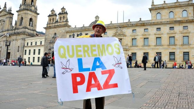 "Man holds a sign reading ""We want peace"" outside the Colombian Senate in Bogota, on November 29, 2016"