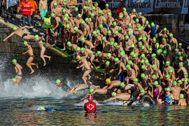 Swimmers jump into the water at the start of the Christmas Crossing 2017 in Gijon, Spain, 25 December 2017