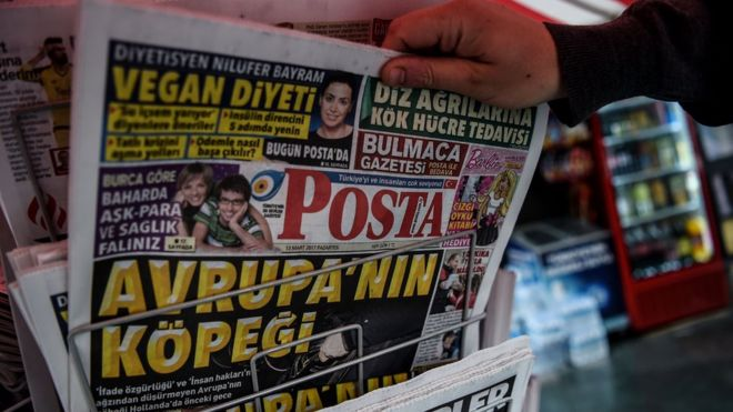 """This picture taken in Istanbul on March 13, 2017 shows a man selecting a newspaper bearing a headline concerning diplomatic tensions between Turkey and The Netherlands, which translates as """"""""Dogs of Europe"""" in Istanbul on March 13, 2017"""