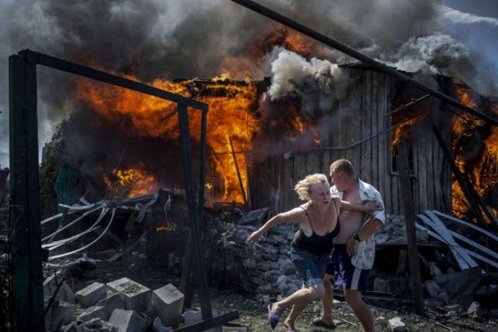 زوجان يفران من احتراق منزل دمرته غارة جوية في قرية لوهانسكايا، في أوكرانيا.
