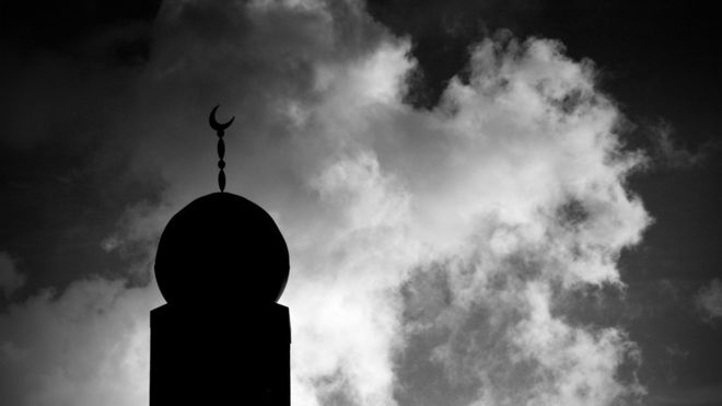 Minaret in silhouette against cloudy sky