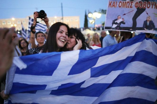 People celebrate in front of the Greek parliament