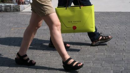 Pair walking with a Ted Baker bag