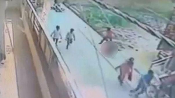Imágenes de una cámara de vigilancia muestran al atacante de pie junto a la mujer, que aparece borrosa.