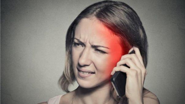Chica usando celular con dolor de cabeza.