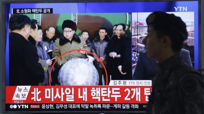 A man walks past TV screen showing Kim Jong-un inspected the alleged nuclear device (9 March 2016)