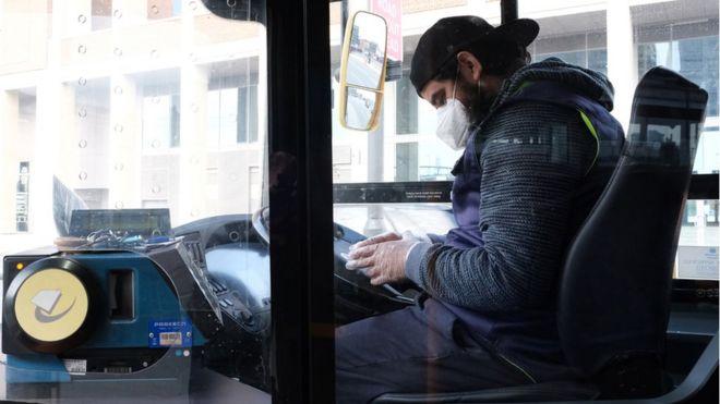 Motorista de ônibus em Londres sentado ao volante usando máscara e luva