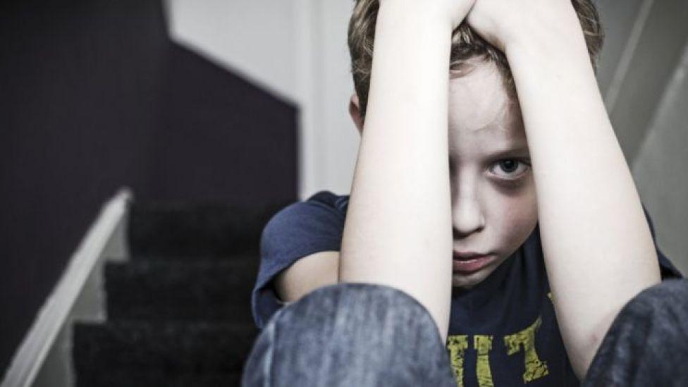 Criança com as mãos na cabeça e feição de preocupação
