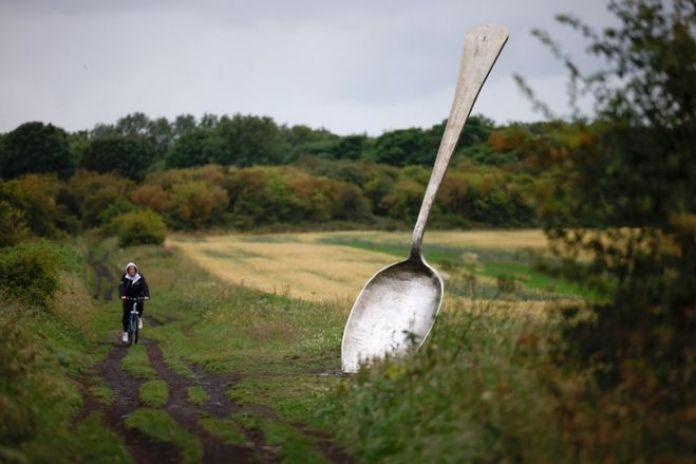 Une personne passe en vélo devant une grande sculpture d'une cuillère au bord d'un champ