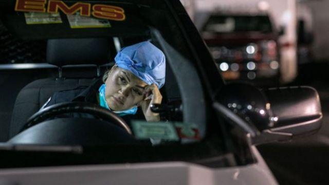 Mujer paramédica recostada contra la ventanilla de una ambulancia
