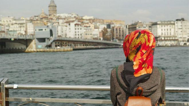 Un autre musulman regarde les bâtiments en face de la mer
