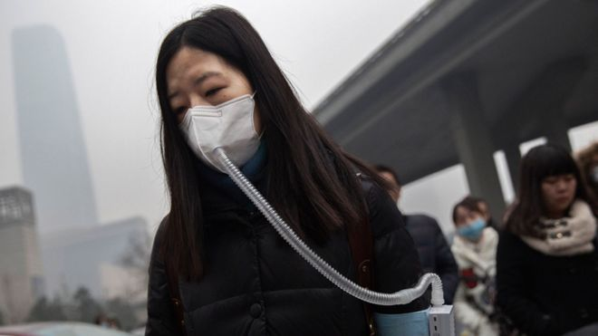 A Chinese woman wears a mask and filter as she walks to work during heavy pollution on December 9, 2015 in Beijing, China