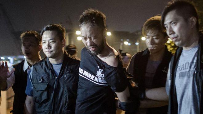 Ảnh chụp ngày 15/10/2014 cho thấy ông Ken Tsang (giữa), thành viên của tổ chức chính trị vì dân chủ Civic Party, bị cảnh sát dẫn đi từ bên ngoài khu văn phòng của chính phủ tại Hong Kong