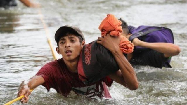 Migrantes caminan por el río para cruzar a México.
