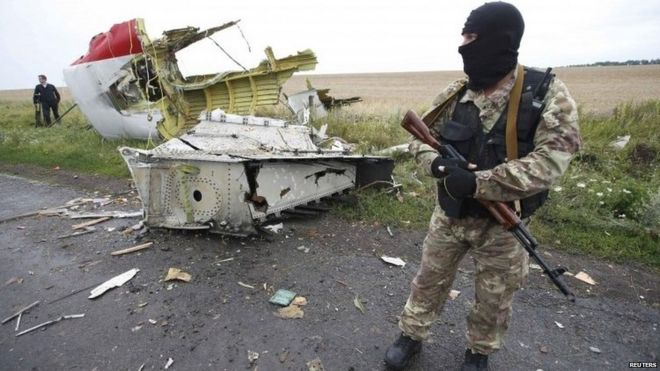 Pro-Russian rebel stands with debris from MH17 - July 2014 picture
