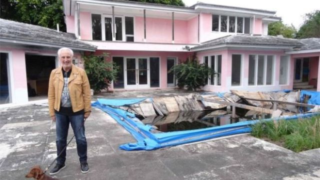 Christian de Berdouare stands with his dog by a pool of a house that used to belong to notorious Colombian drug lord Pablo Escobar on January 13, 2016, in Miami Beach, FL.