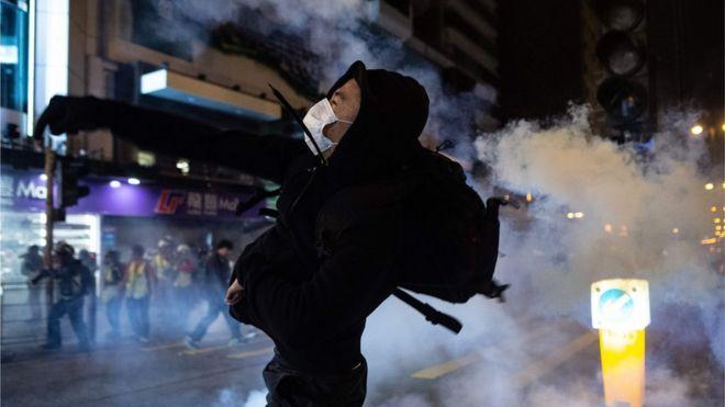 抗議者は、警察が催涙ガスを発射した後、香港のヨルダン地区での抗議行動で傍観者を解散させた後、2019年12月25日に反応する