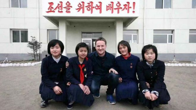 Canadian businessman Michael Spavor poses with girls at a school in Rason Special Economic Zone, North Korea