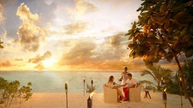 Imagem mostra casal sentado à mesa e sendo servidos com bebida no resort de luxo The Brando