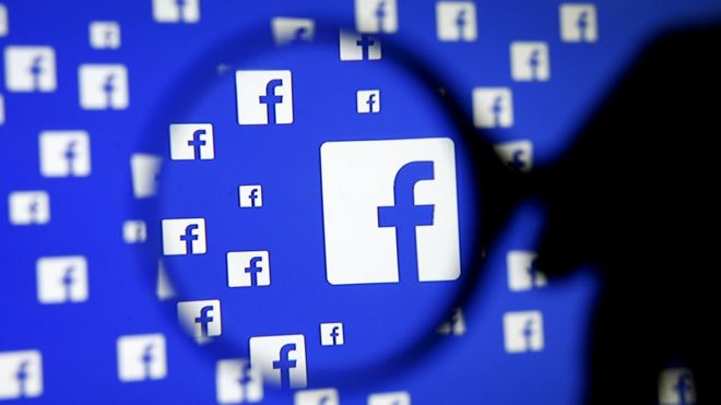 A man poses with a magnifier in front of a Facebook logo