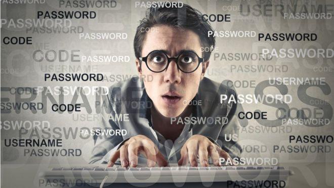 Geeky homem digitando no teclado rodeado por gráficos de senha