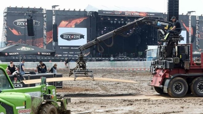 A worker lifts a board at the Rock am Ring music festival (04 June 2016)
