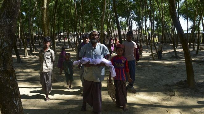 A Myanmar Rohingya refugee carries the body of six-month-old Alam for his burial in a refugee camp in Teknaf, in Bangladesh's Cox's Bazar district, on November 26, 2016.