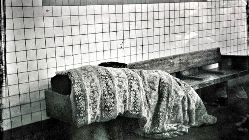 Una persona sin techo en el metro de Nueva York.