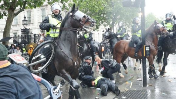 An injured police officers is attended to after falling off her horse