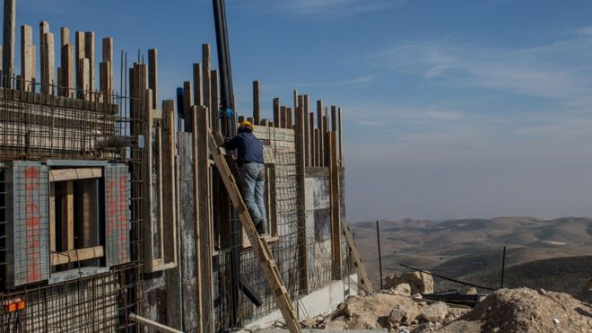A Palestinian worker builds a new house in an Israeli settlement on 16 January 2017 in the West Bank