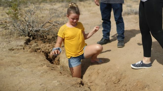 Una niña que vive en Ridgecrest introduce su pierna en la grieta creada tras el terremoto.