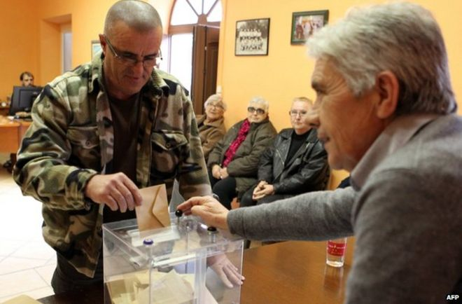 A man casts his ballot during the first round of the French departmentals elections on 22 March 2015 in Corsica
