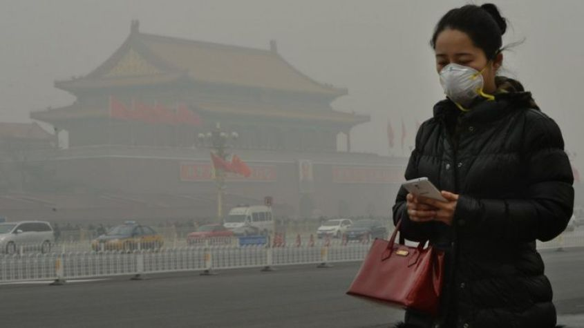 A woman walks beside Tiananmen Square as heavy air pollution continues to shroud Beijing on 26 February 2014